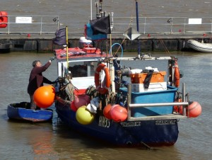 A local fisherman painting his boat. in Harwich, Halfpenny pier.