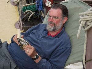 Reading a book on the schooner Trinovante