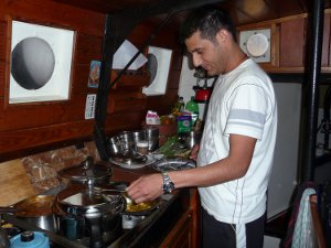Ajay cooks up a curry on a SchoonerSail sailing holiday.