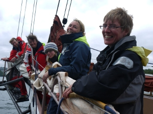 The new schooner crew out on the bowsprit furling the jib.