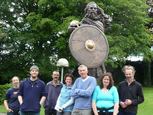 The crew stand before a statue of Earl John in his prime.