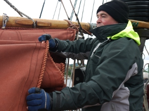 Marcel furls the gaff mainsail.